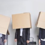 Moving problems force business people to cover their heads with cardboard boxes