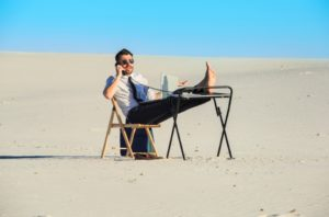 What moving your office to the beach looks like: man with a desk in the sand