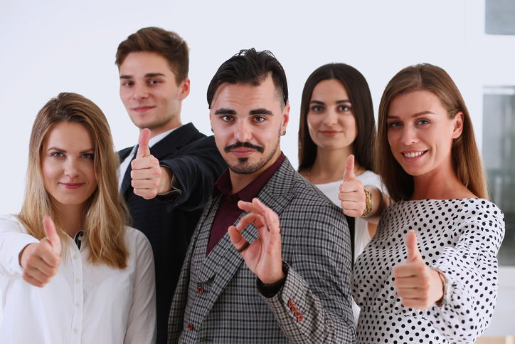 office staff giving thumbs up for a great work environment